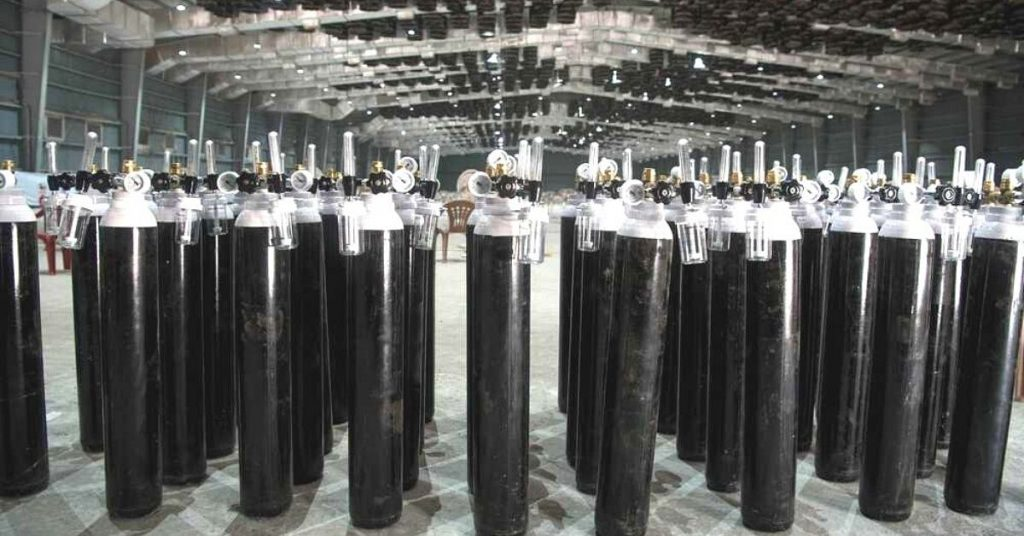 oxygen cylinders standing stacked in a warehouse