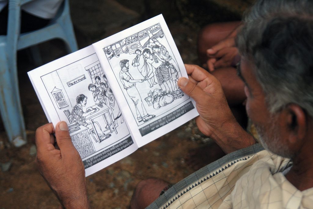 a migrant worker reading a booklet on bonded labour-migrant workers' rights