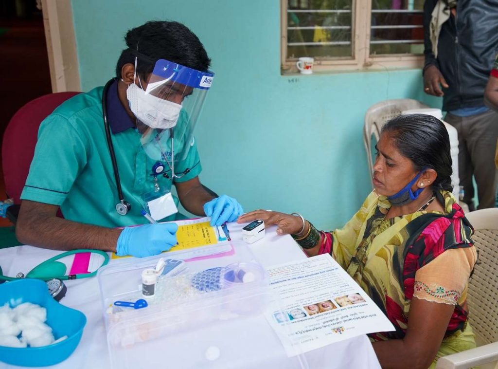 A woman getting her oxygen levels checked by a person wearing a mask and face shield_COVID-19_second wave_vaccine hesitancy_picture courtesy: Trinity Care Foundation/Flickr
