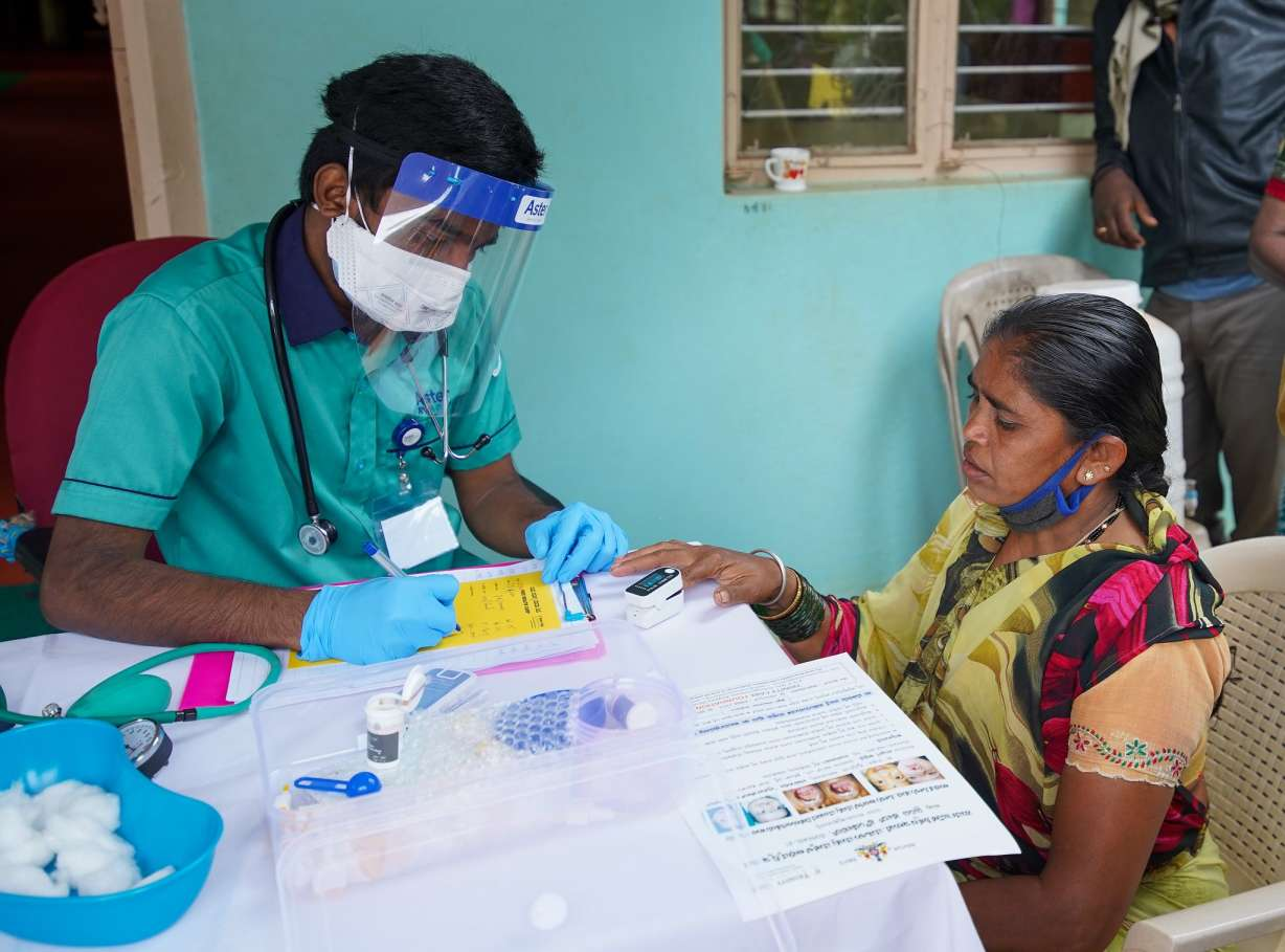 A woman getting her oxygen levels checked by a man wearing a mask and face shield_courtesy_Trinity Care foundation_Flicr_COVID-19_second wave_vaccine hesitancy