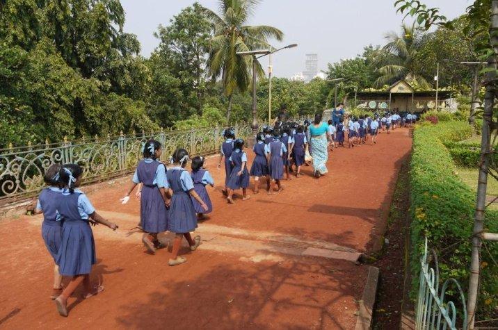 Girls wearing a uniform walking in a line in a garden-adolescent girls COVID-19 education