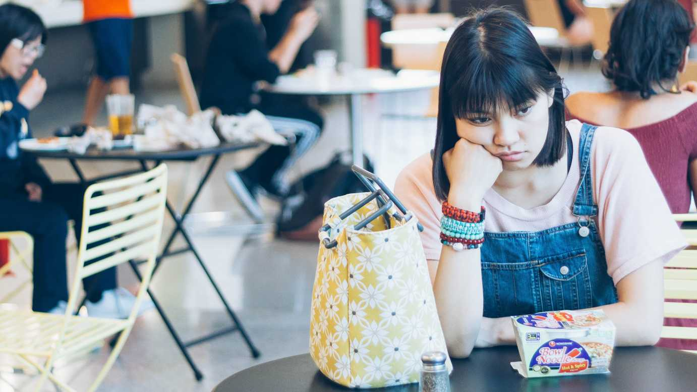 picture of a girl sitting at a table in a cafeteria and looking sad-collective well-being