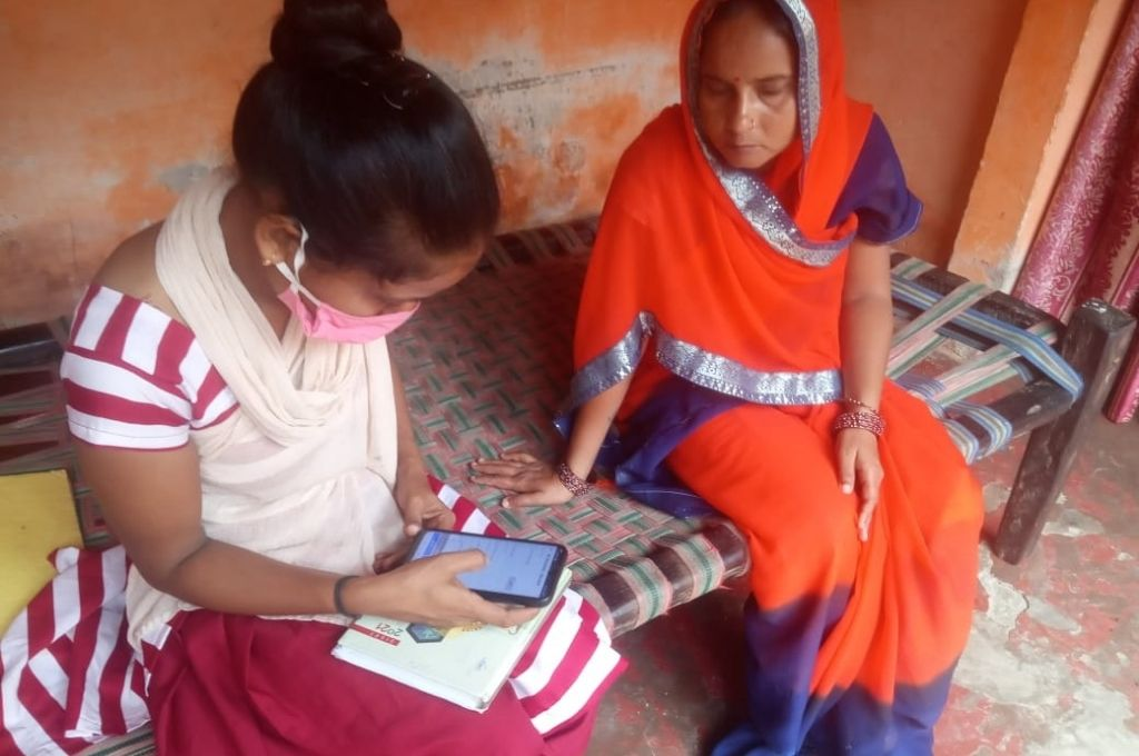 A woman wearing an orange saree watching a girl wearing a mask operate a mobile phone. The article that funders in the social sector have an incredible opportunity and obligation to change our one-way relationship with data.