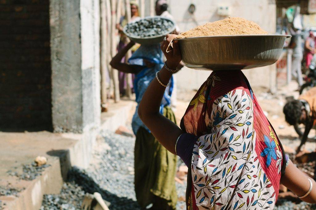 Two women in sarees, carrying construction materials on their head. The photograph has been clicked from behind. NREGA is crucial to the rural economy of India, especially in 2021 with low yield and poor monsoon