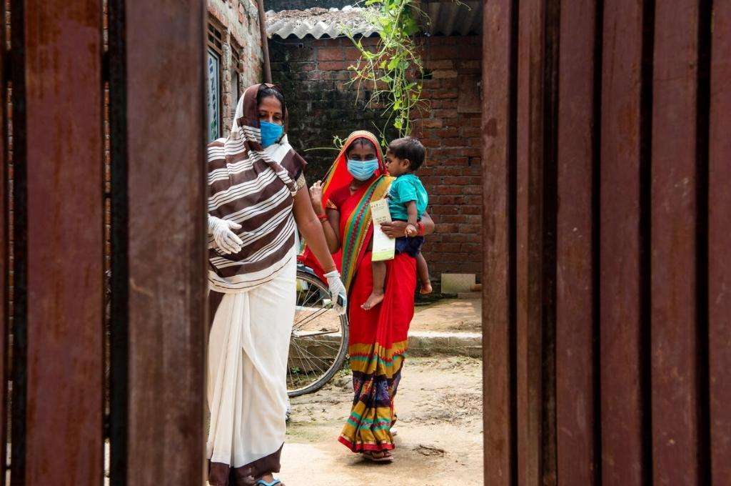two masked women standing; the woman to the right has a baby in her arms-