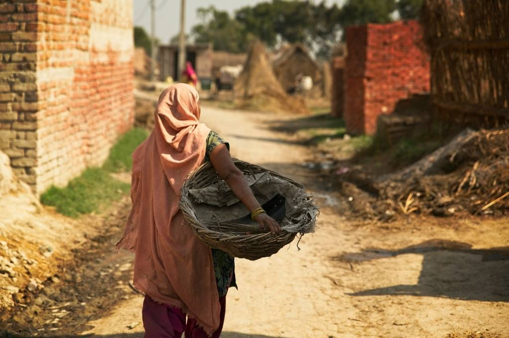 the back of a women holding an empty waste basket against the backdrop of an empty street lined with brick buildings-manual scavengers