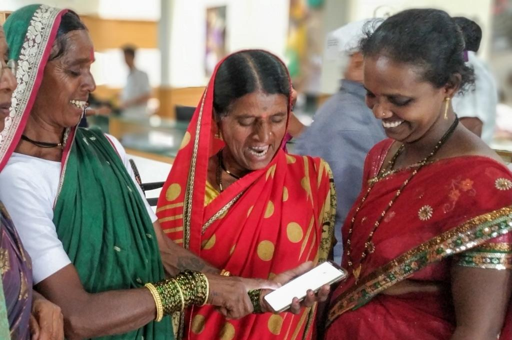 three women looking at a smartphone and smiling-