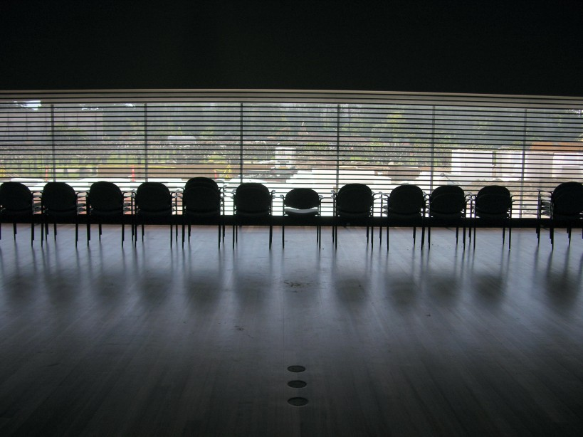 A row of empty chairs lined up in an empty room_board members