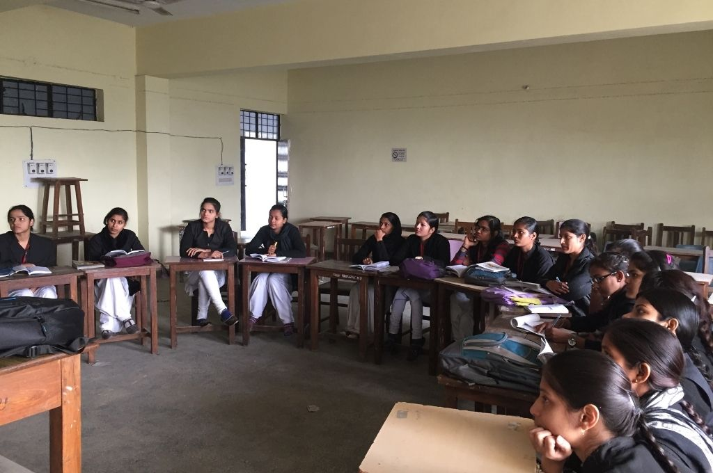 Girls in a classroom, listening to a lecture. A nonprofit learns the importance of strategy and communication when planning for scale.