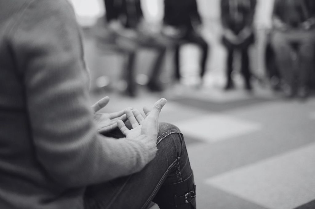 Image of the hands of a person at a group therapy session. Suicide prevention requires community effort and policy changes