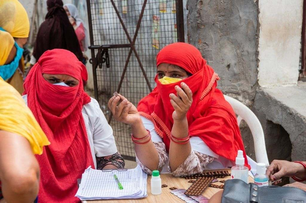 Two Ashas, their face covered with red dupattas, giving medicines to a person. Community healthcare workers were crucial to India's COVID-19 response. They need better pay and training for their well-being.