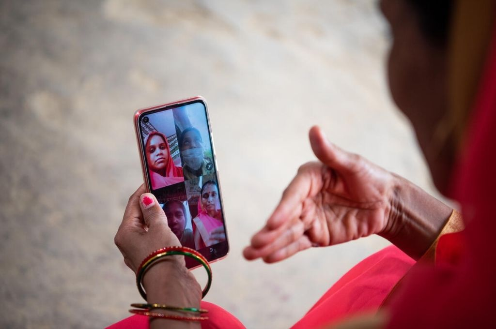 an aanganwadi worker video calling a group of women beneficiaries on a smartphone for telecounselling-COVID-19 awareness campaigns