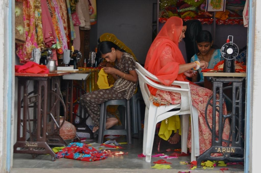 four women sitting on chairs on a fabric shop working on stitching clothes in a tailor shop-livelihoods programmes