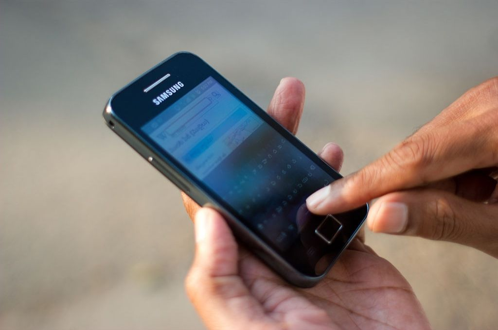 image of a phone in the hands of someone attempting to type-technology for nonprofits